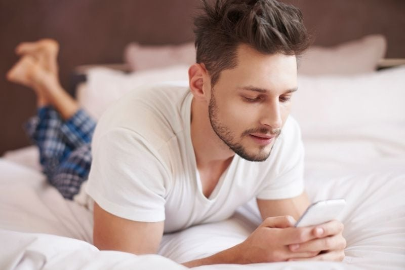 man lying down on bed reading text message from cellphone