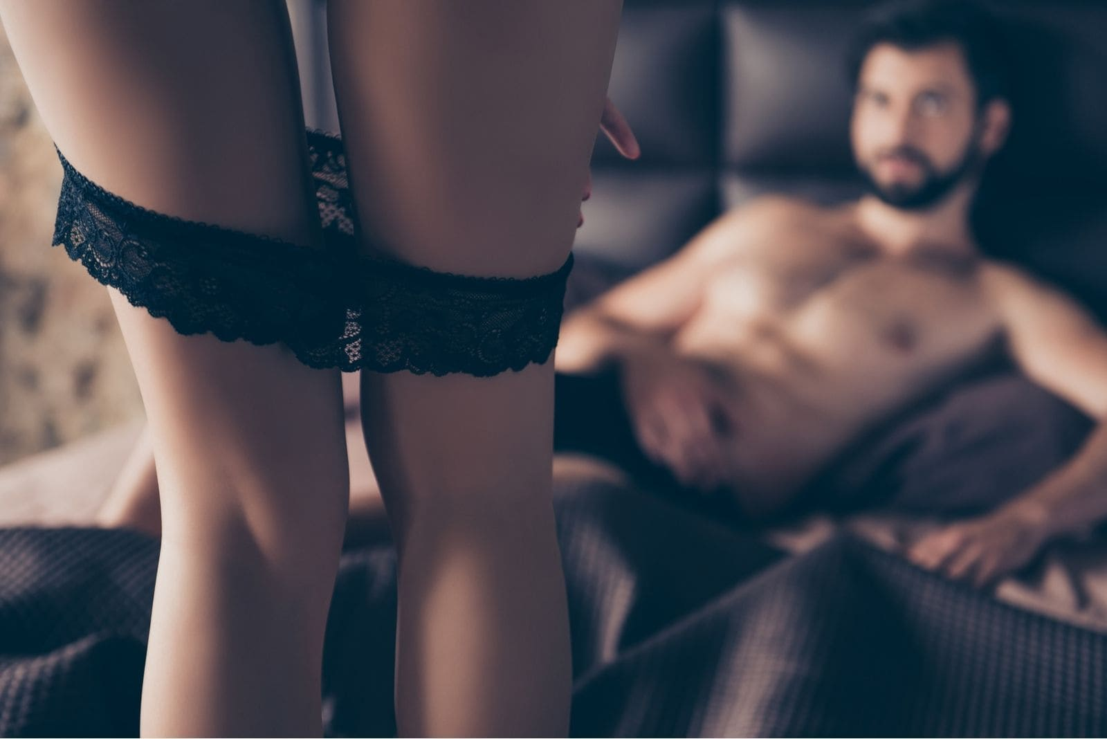 man lying down in bed watching a woman taking off her undies