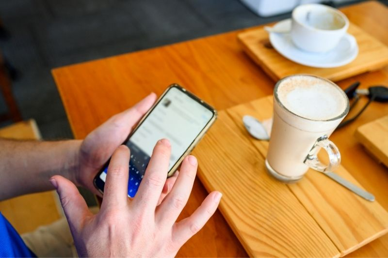 man on phone's posting social media inside a cafe in cropped image