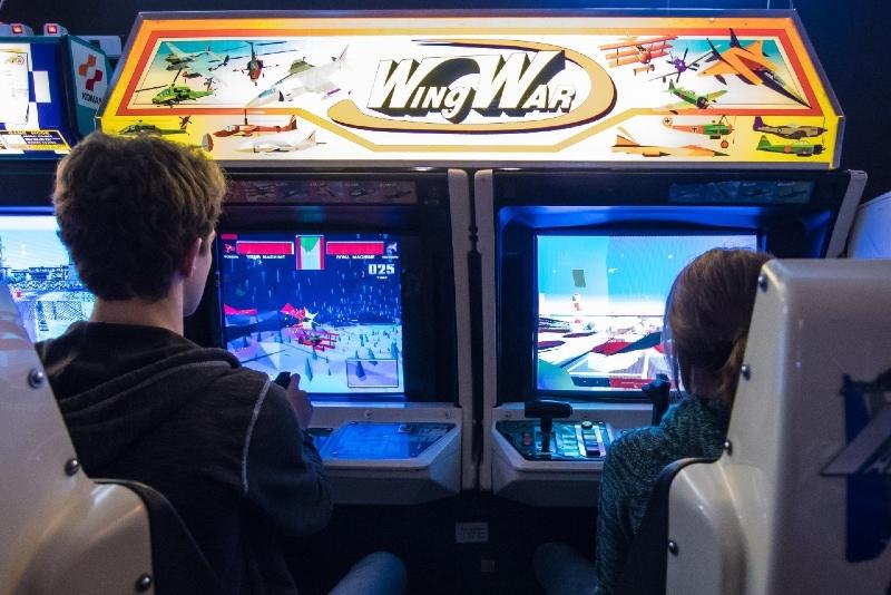 man in black jacket playing arcade game