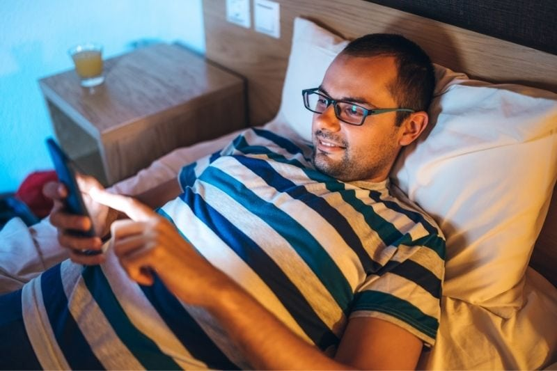 man reading messages from his smartphone while lying on bed