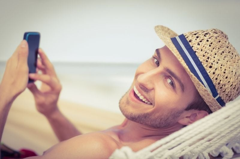 man relaxing in hammock texting on smartphone and smiling looking at the camera behind him