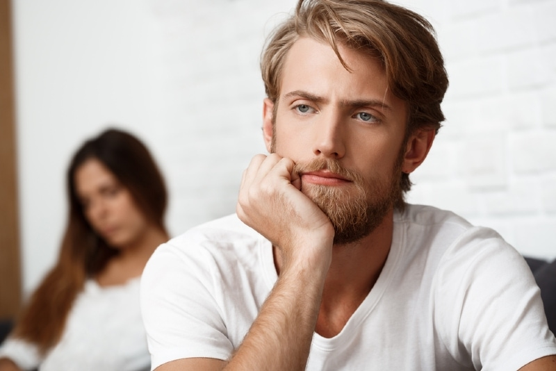 sad man in white t-shirt sitting near woman
