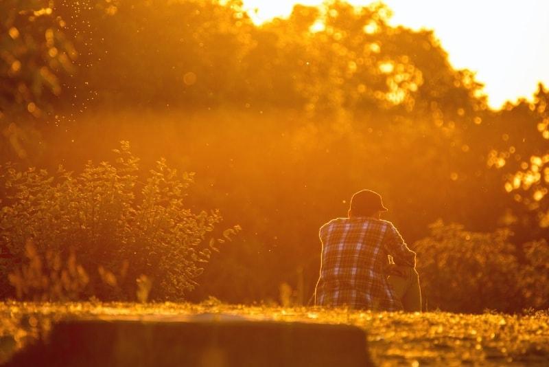 man with black cap sitting on grass