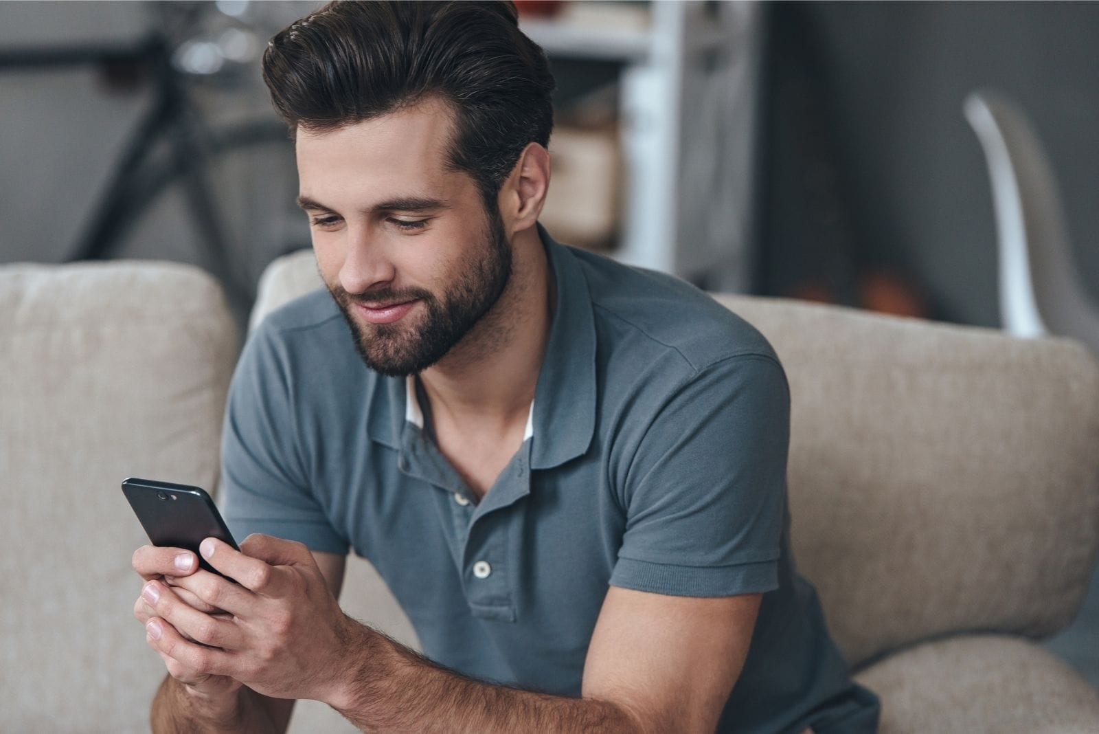 man smiling and texting while sitting in couch in casual shirt