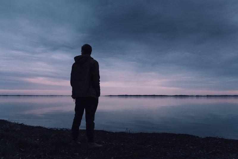 man in black jacket standing near lake