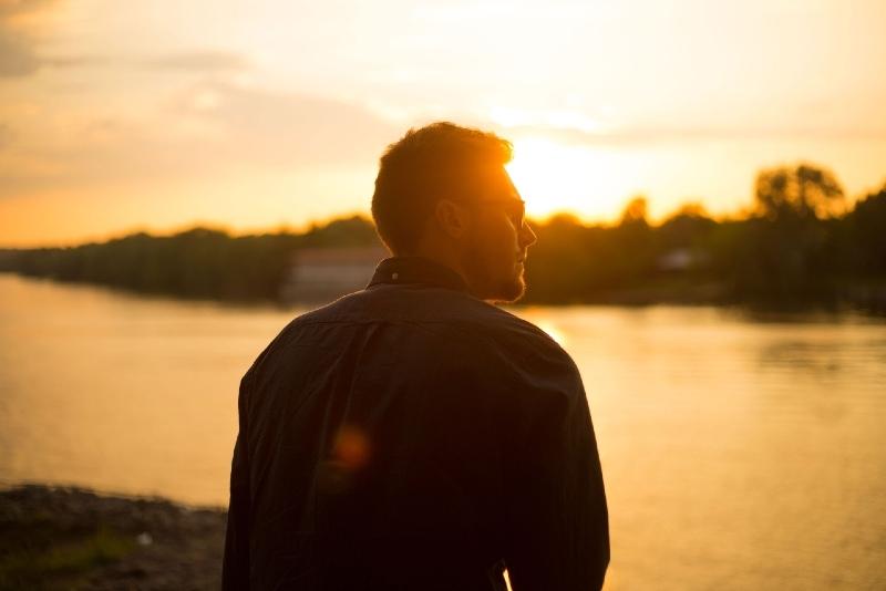 man standing near water during sunset