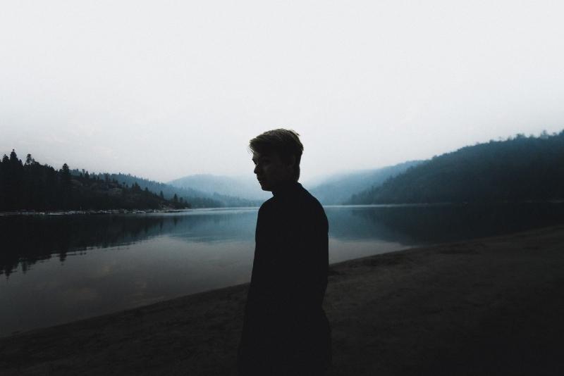 man in black turtleneck sweater standing near water