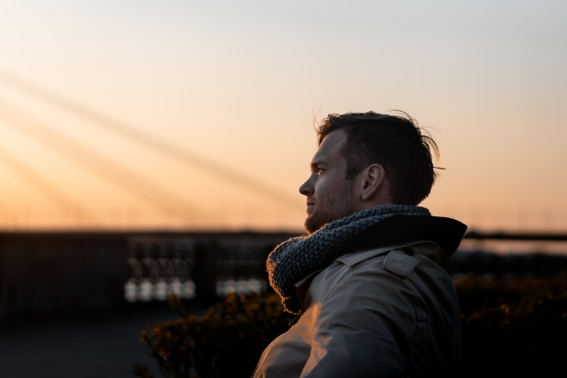 man with gray knit scarf standing outdoor during golden hour