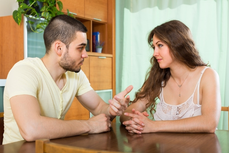 man talking to woman while sitting at table
