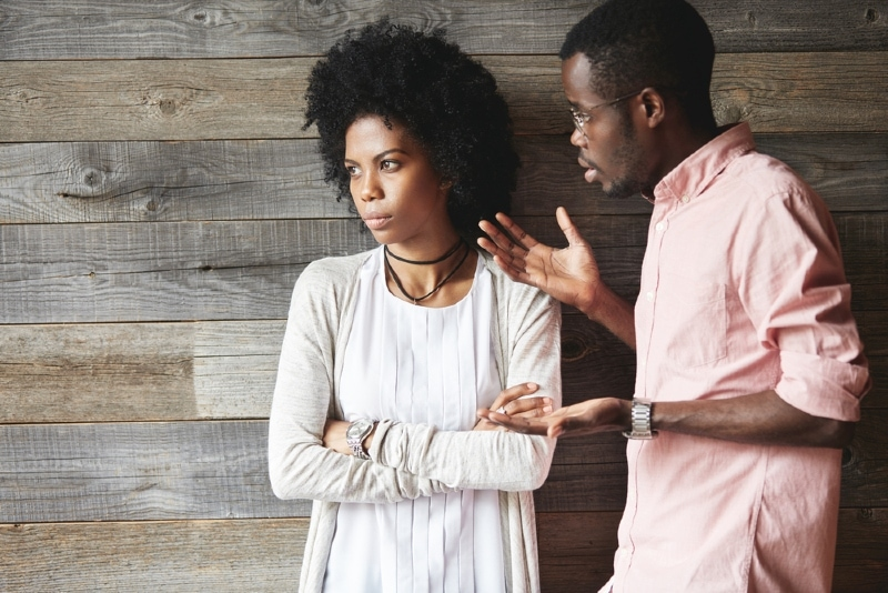 man talking to woman while standing near wooden wall