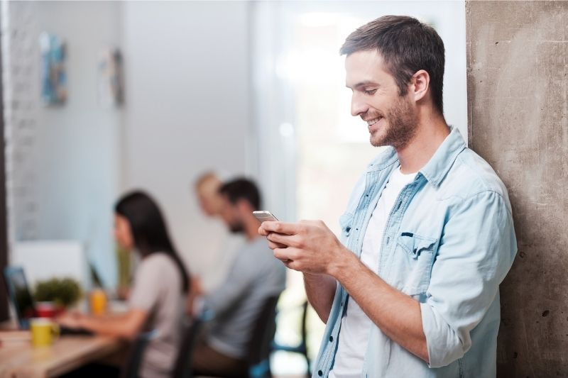 man texting and smiling while standing and leaning on a wall with colleagues working