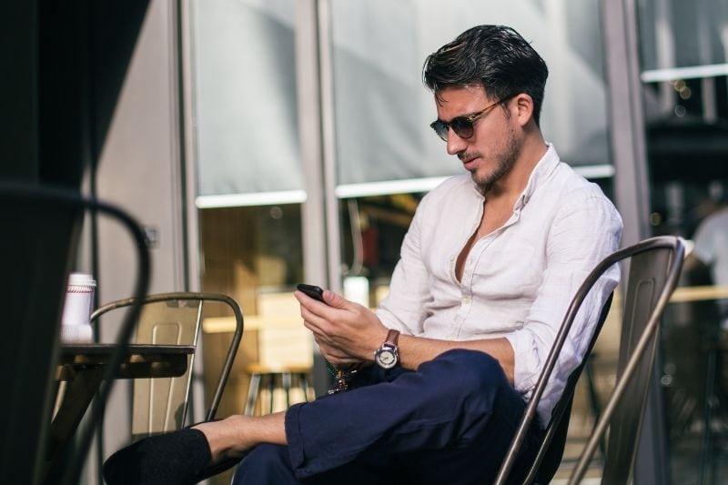 man texting in a cafe wearing sunnies outdoors