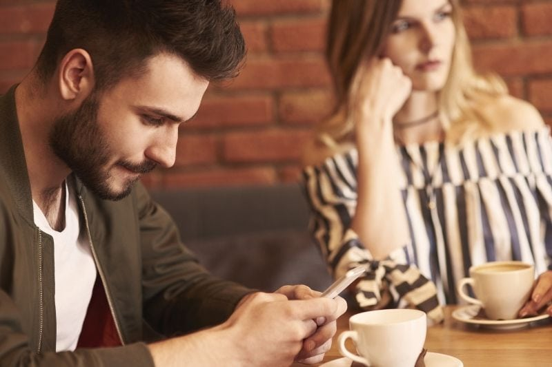 man texting in his cellphone during a date with a woman looking bored and looking away