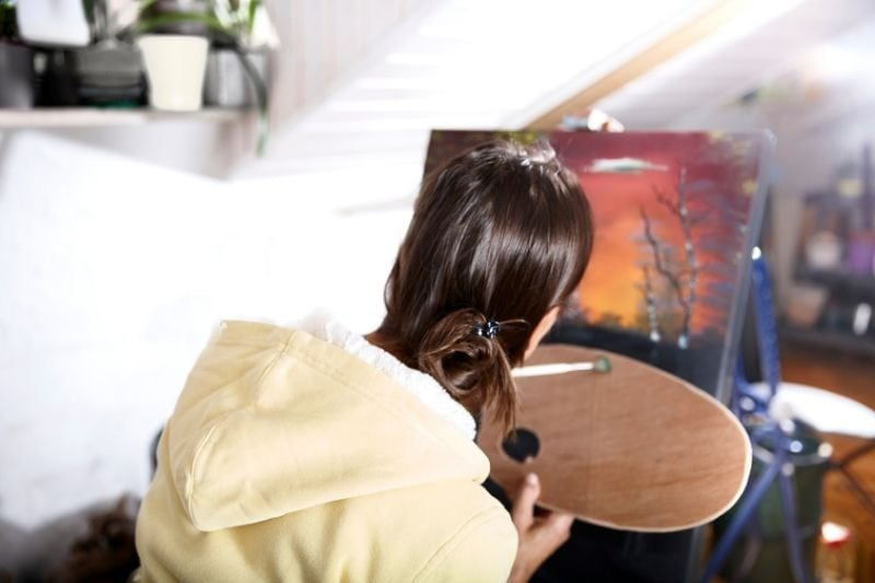 mature woman painting in oil canvass inside an art room