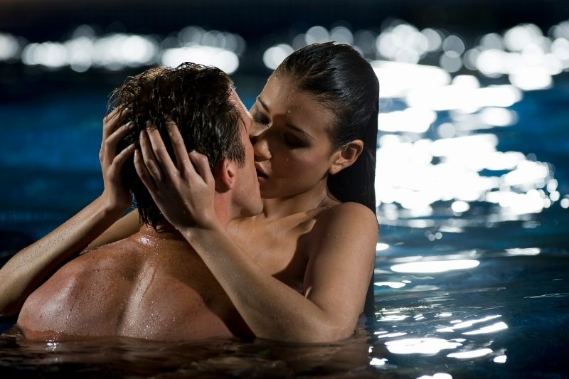 naked couple kissing in the swimming pool at night