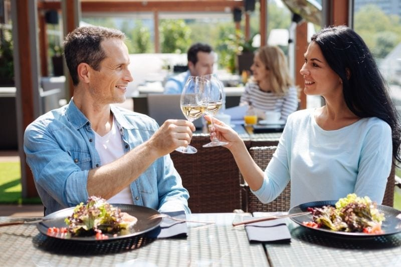 nice positive man and a woman having a date in an outdoor restaurant