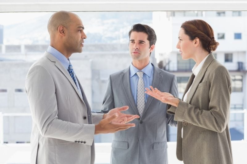 office business colleagues disagree and argue while standing thru the buildings hallway