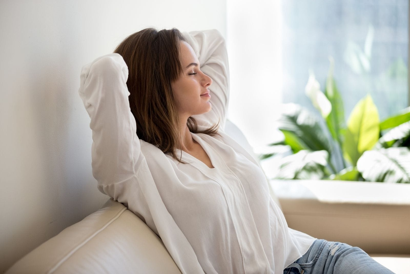 peaceful calm woman sitting on the couch while hands on her head