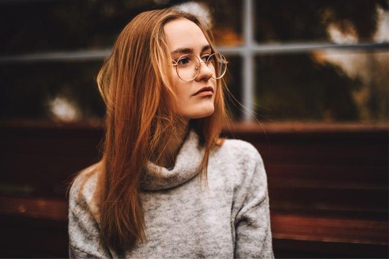 pensive brunette woman with eyeglasses looking away