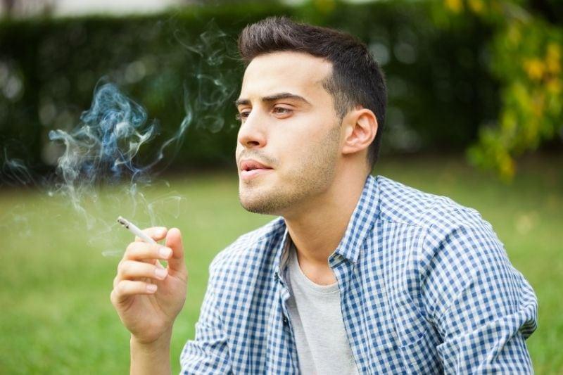 pensive man smoking cigarrette outdoors while sitting