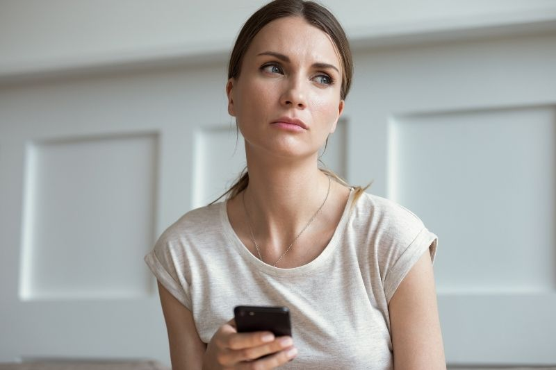 pensive thoughtful woman at her 30's holding a cellphone wearing white top inside the house