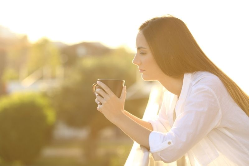 pensive woman in the balcony holding cup during sunset