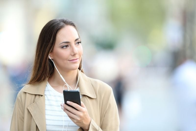 pensive woman listening to music from her smartphone while walking outside