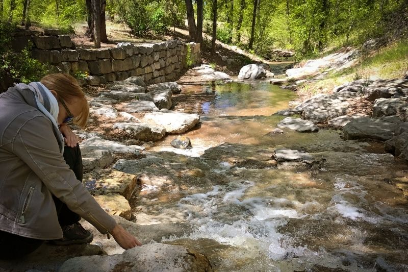 pensive woman near stream touching the water flowing