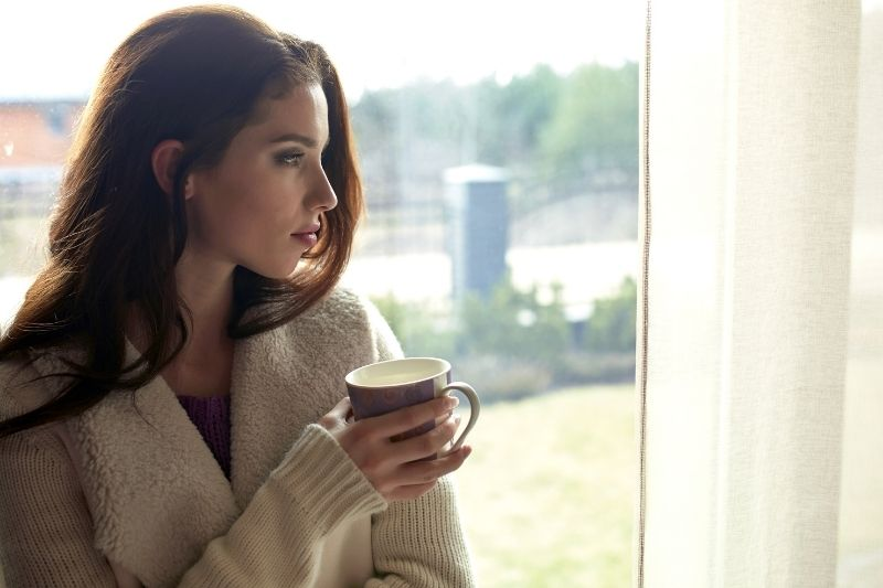 pensive woman sipping coffee early in the morning near the glass window