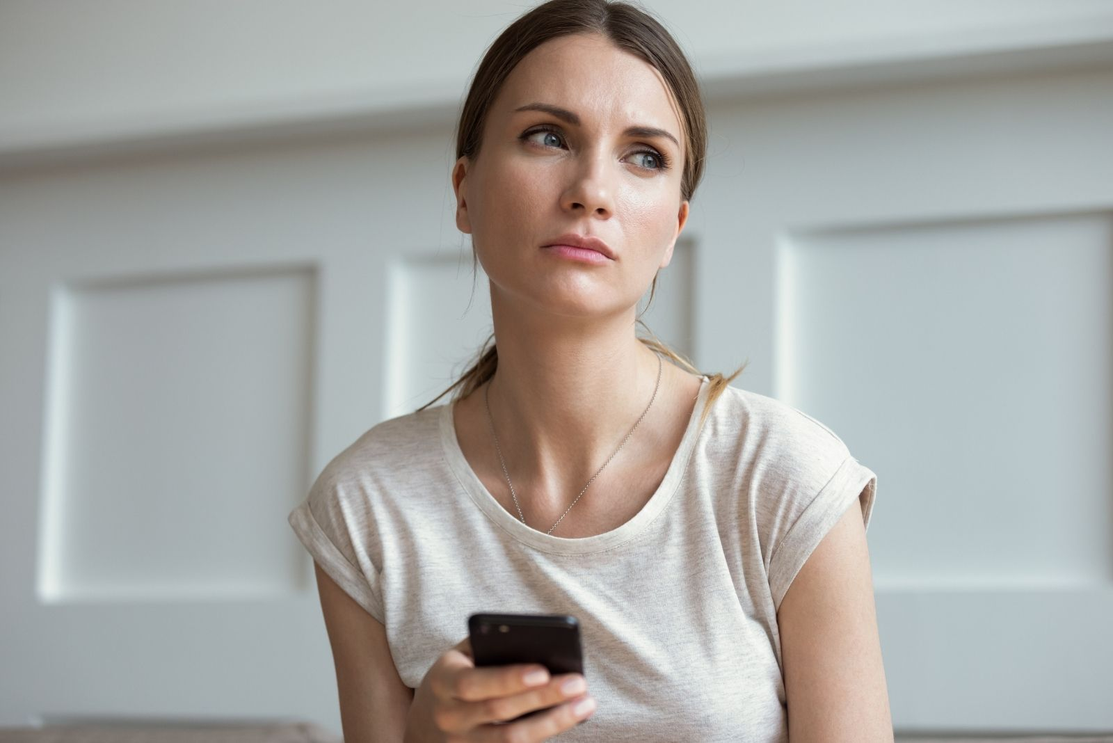 pensive woman texting on smartphone inside home
