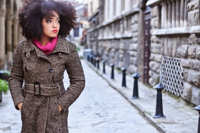 pensive woman walking on the street with hands inside the pocket of her coat