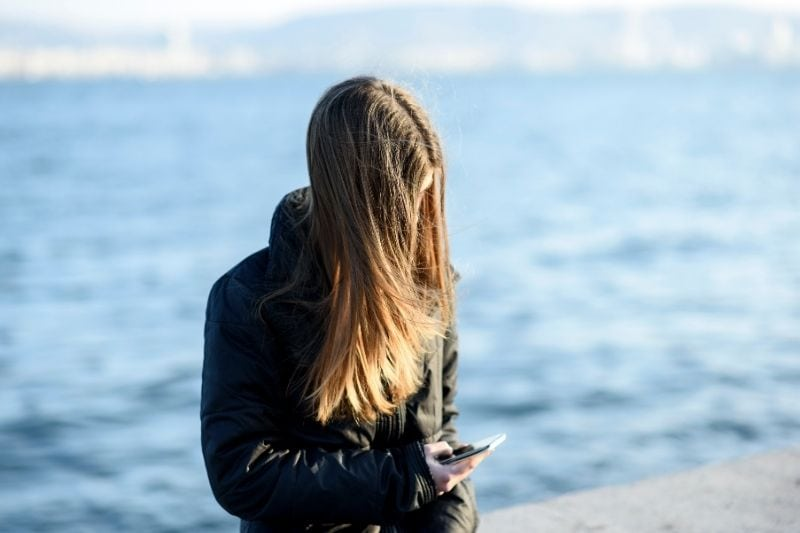 pensive young woman in jacket texting and standing and leaning in the breakwater near the sea