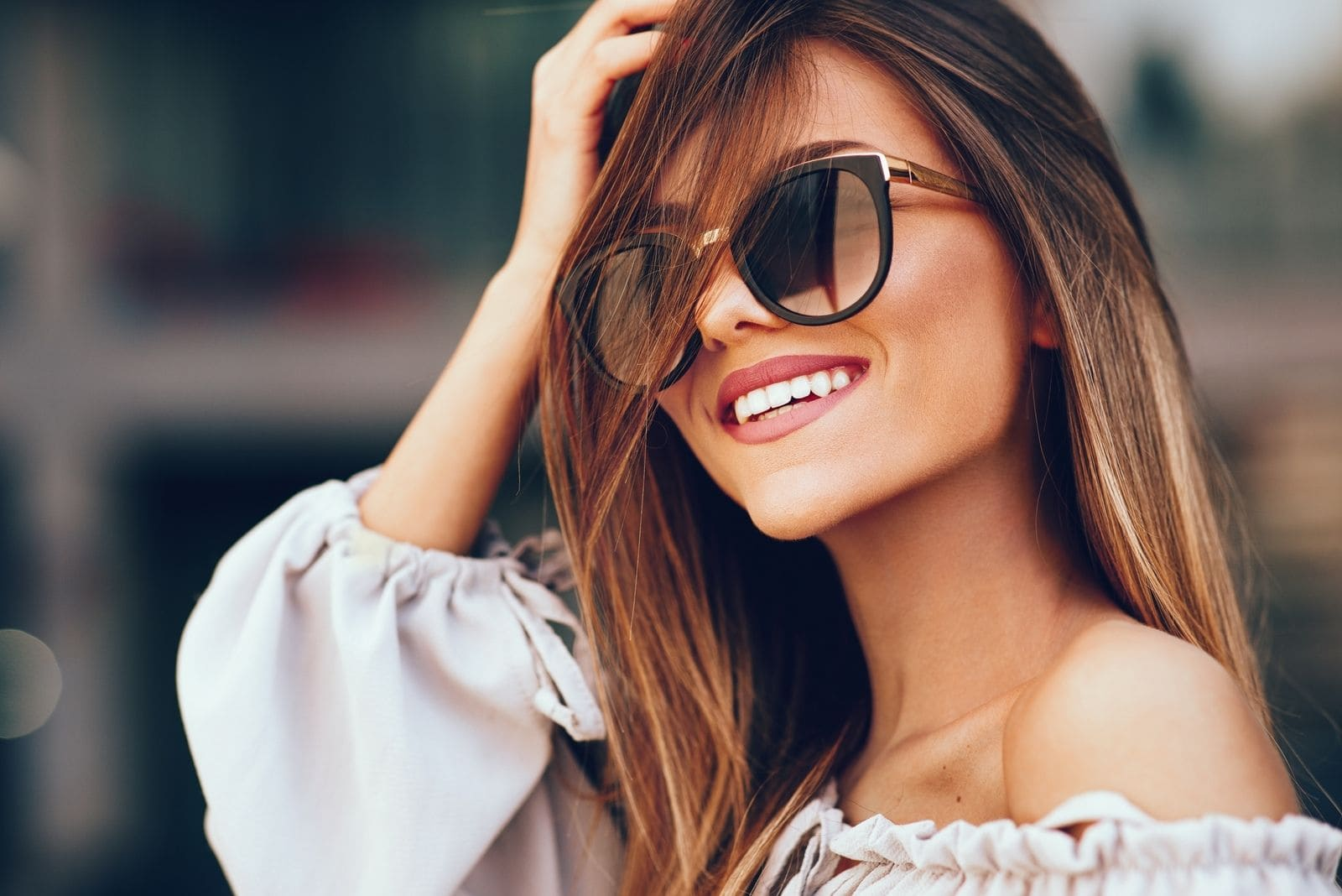 portrait of a beautiful woman smiling wearing a sunglass and holding her head
