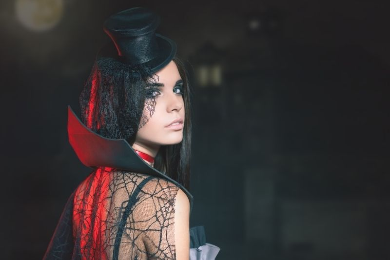 portrait of a sexy woman with a gothic makeup smoky eyes in a dark place