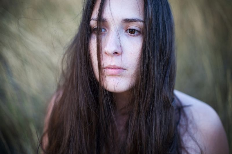 portrait of a woman introspecting deeply with unkept brown hair