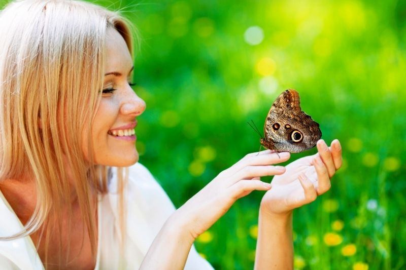 pretty blonde woman playing with the butterfly in the spring park
