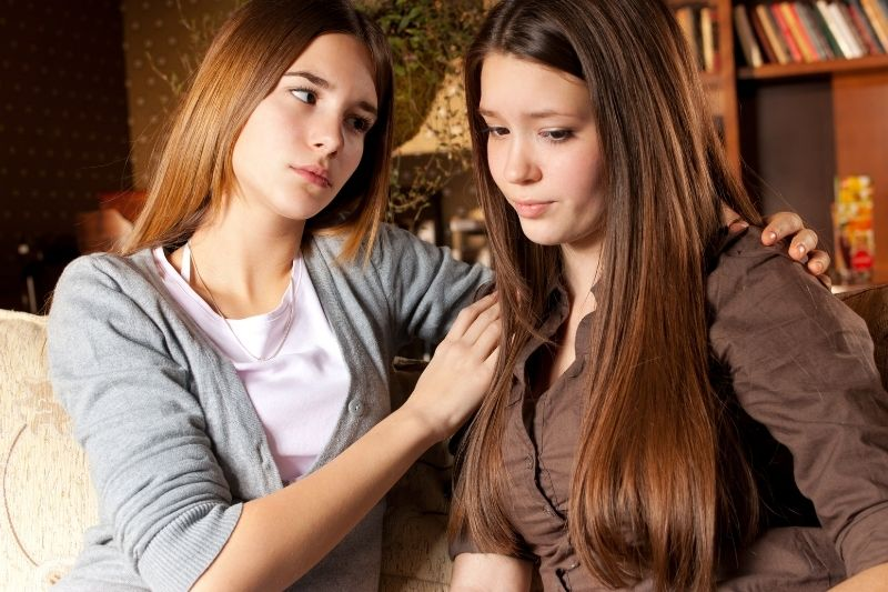 pretty girl consoling a sad depressed woman inside while sitting inside the house