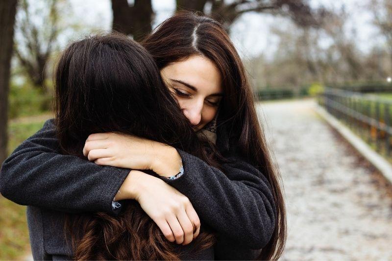 pretty girl hugging her best friend in the park