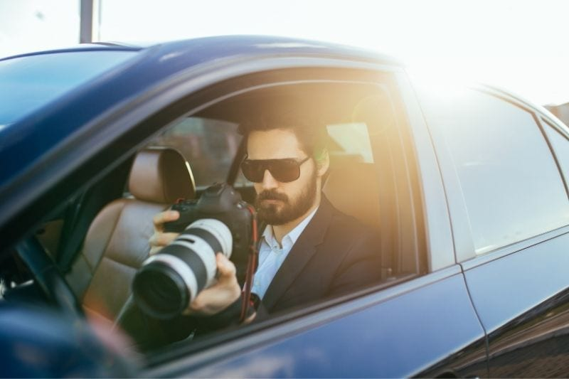 private detective investigating using a binocular while sitting inside the car