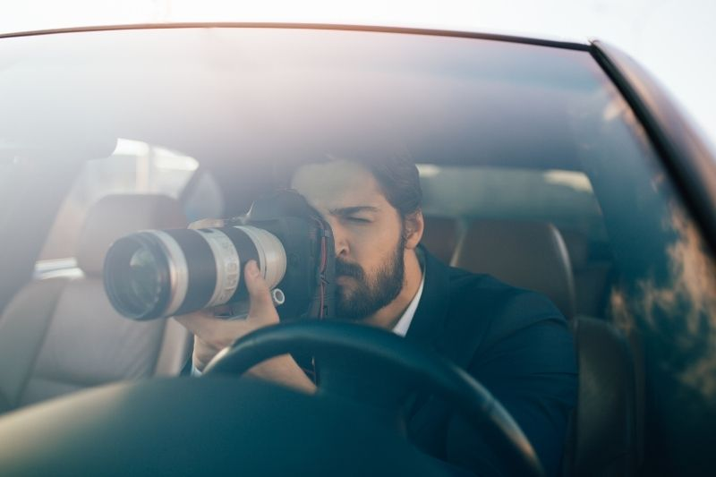private investigator looking thru the camera while sitting inside the car