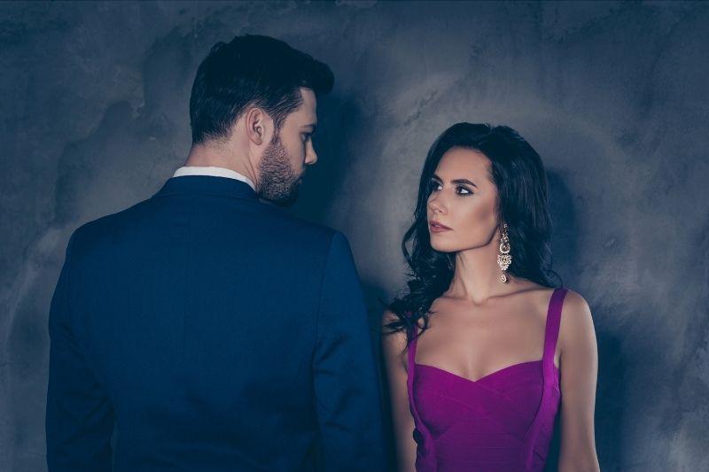 rear view of a man in tuxedo beside a woman in purple dress looking at him