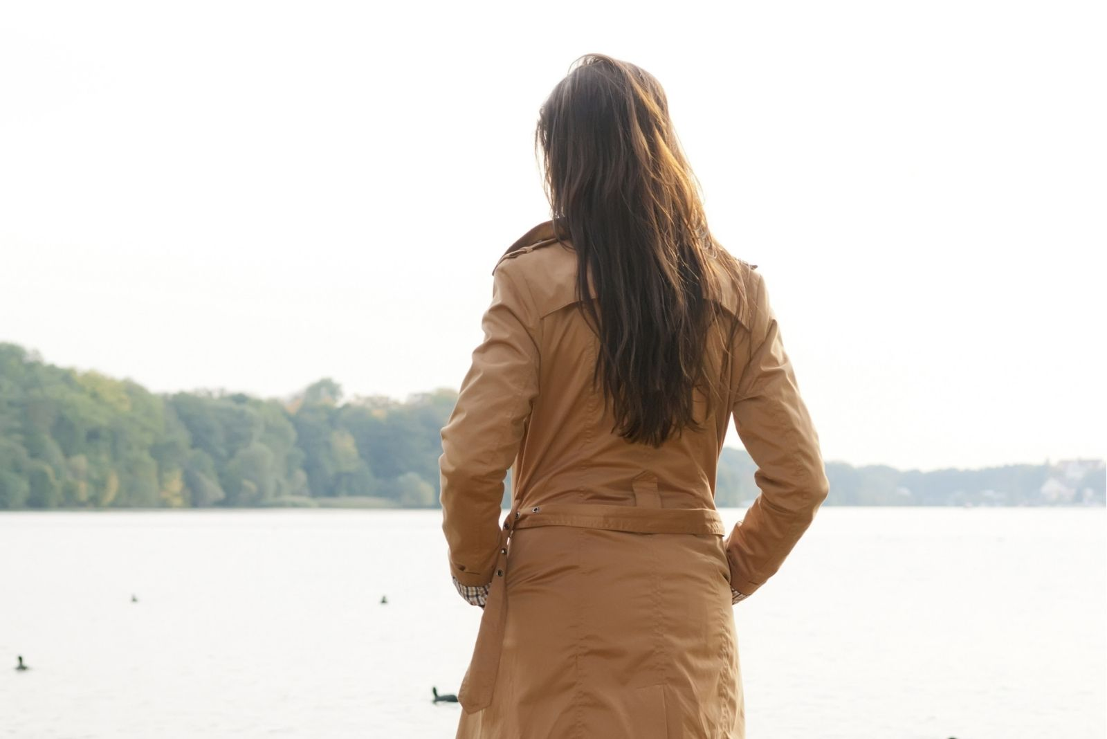 rear view of a woman facing the lake or body of water