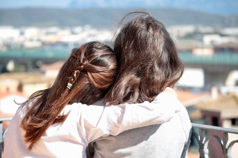 rear view of best friends hugging at a veranda looking at the city