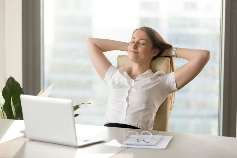relaxed woman closing eyes inside the office leaning on the chair and smiling