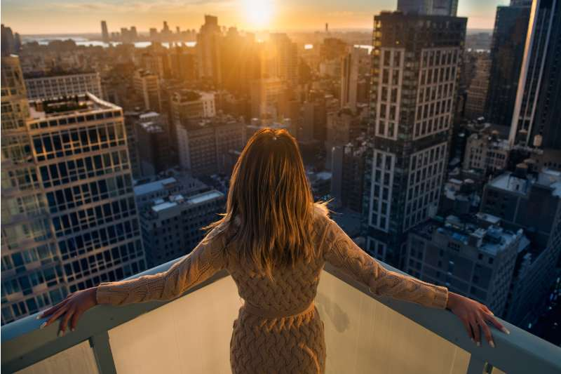 rich woman enjoying the sunset at the top of the high building