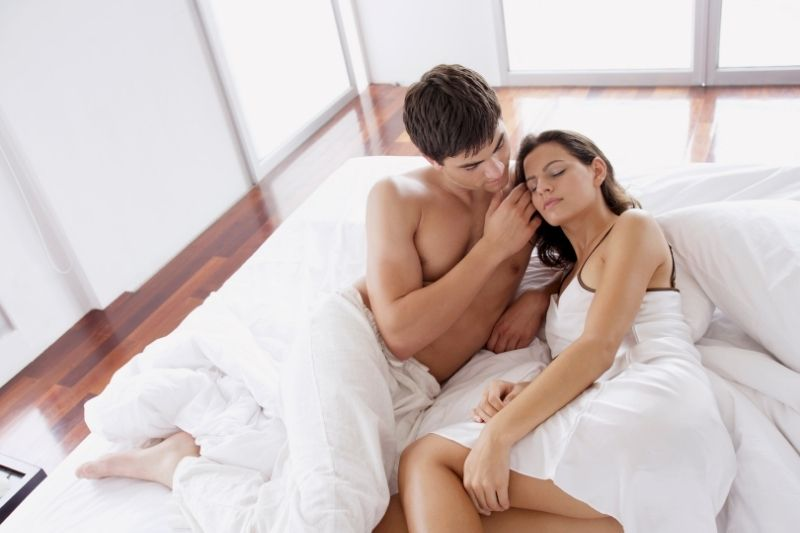 romantic couple in bed man shirtless and caressing the woman