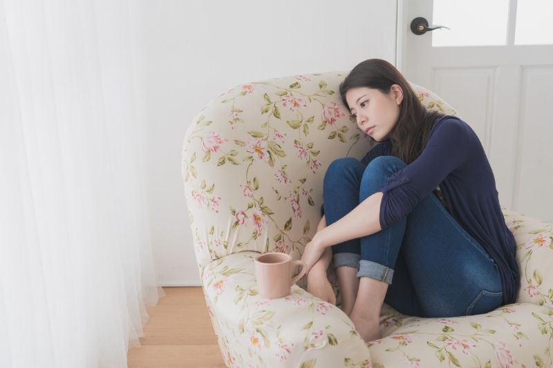 sad woman sitting on couch feet tucked and a cup on a corner of the house