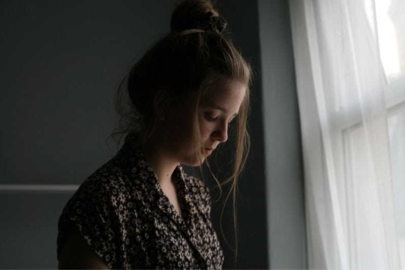 sad woman standing near the curtains of window