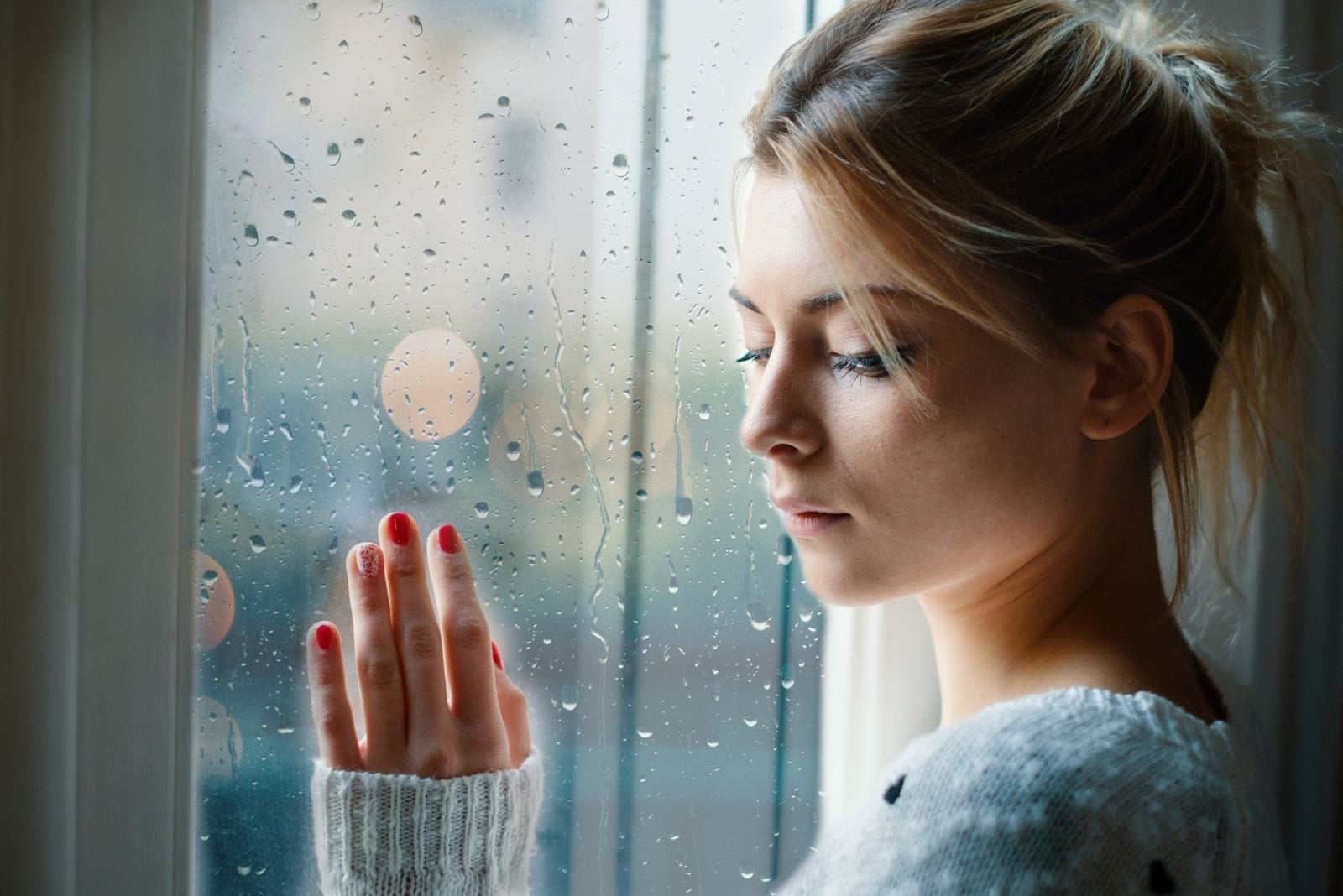 sad woman touching the glass windows with raindrops